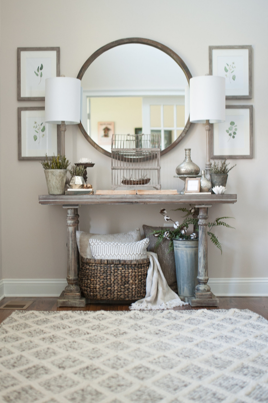 An inviting entryway, a cozy rug, end table with matching lamps, artwork to look at and large round mirror.