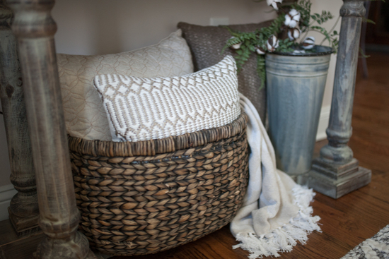 Large woven brown basket containing cozy white and oatmeal colored pillows and a throw blanket.