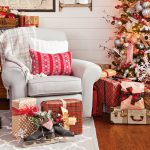 A cozy light colored armchair sat next to a sparkly lit Christmas tree surrounded by gifts.