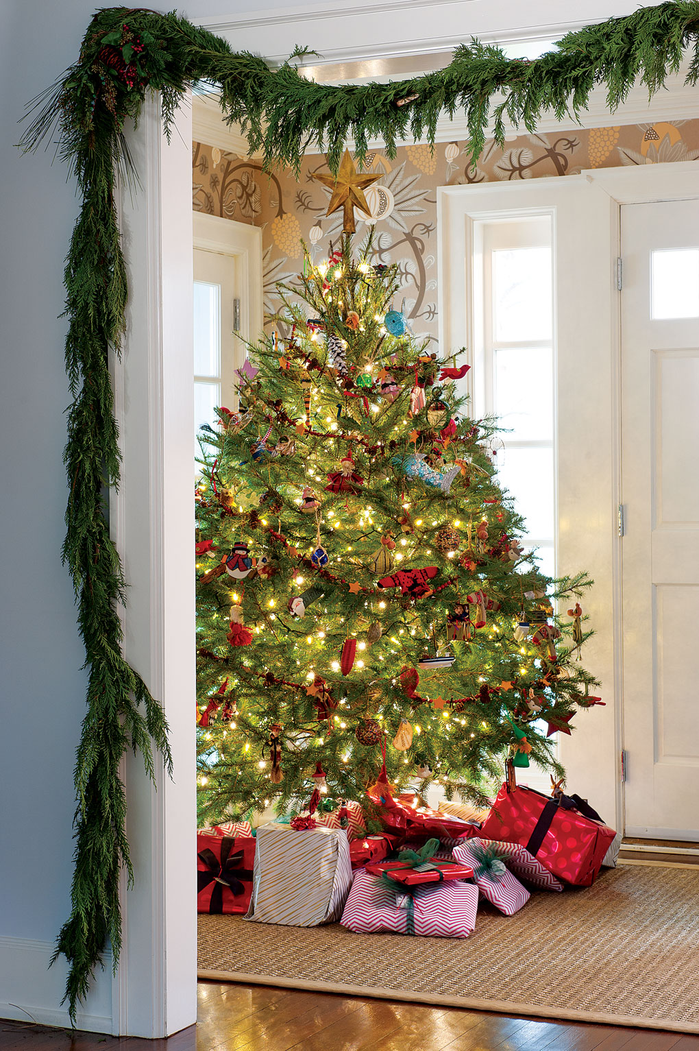 Pine garland frames a large entryway and a well-lit Christmas tree stands near the front door in the foyer.
