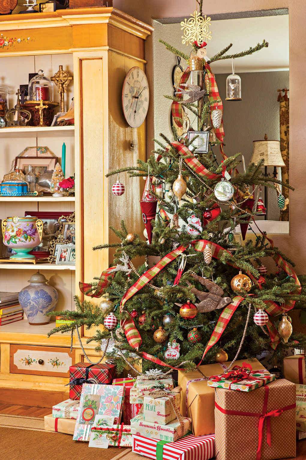 Charlie Brown tree style with sparse branches but tons of character with ribbon and ornaments and present stacked around the bottom.