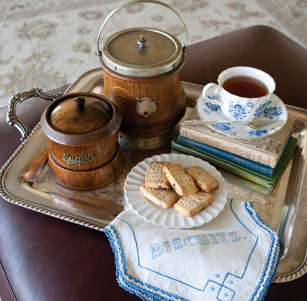Antique wooden tea and sugar containers set out on a silver tray with tea and biscuits.