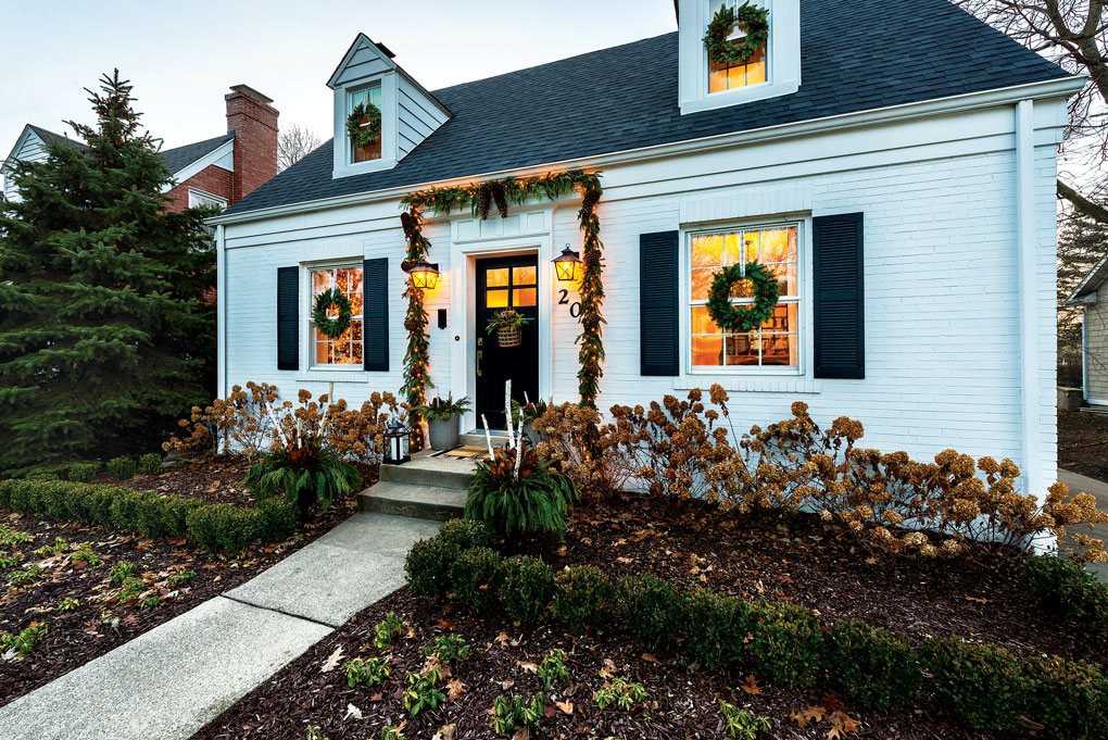 Charming cape cod styled home with a dormers and Christmas wreaths hanging on the front door and in front of each window.