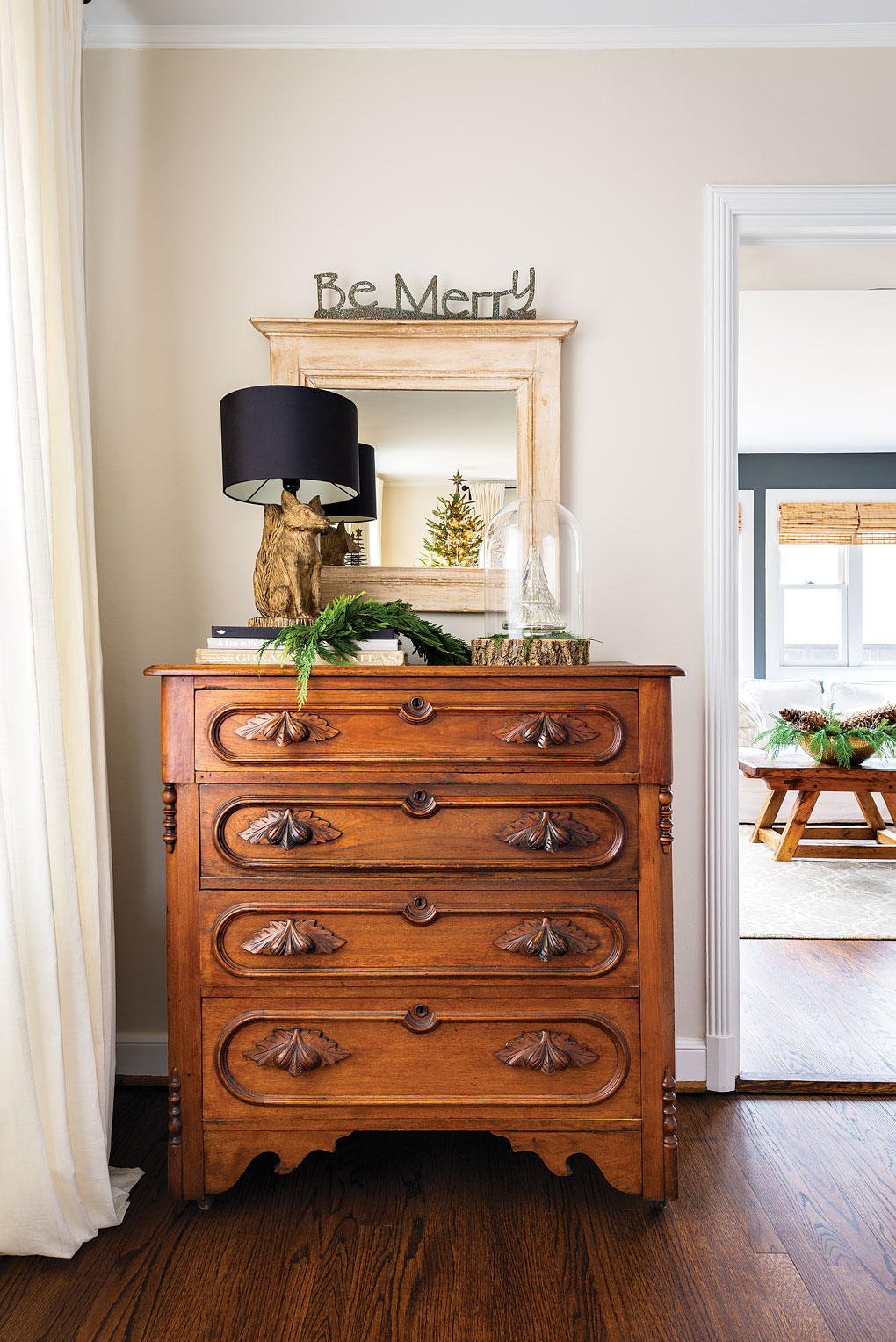 An antique and ornate wooden dresser with a mirror and a fox lamp on top accented with fresh greenery.