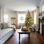 Wide shot into a simply lovely family room with light gray couch placed across from a candle-filled fireplace with a lighted Tree in the background and white stockings hung by the front door.