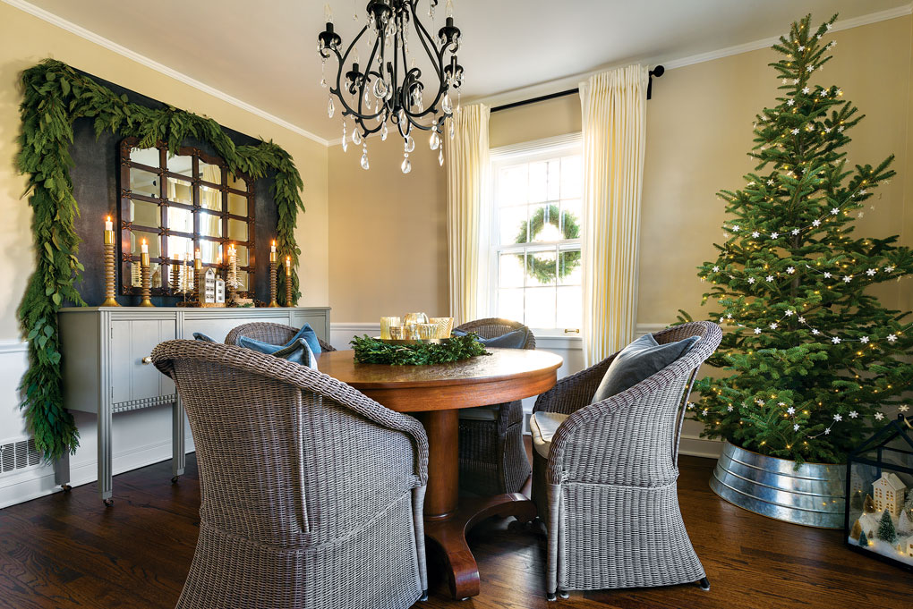 Wicker chairs in gray surround the dining table while a black and crystal chandelier centered above it. Real greenery in the form of a garland and a Christmas tree add color to the room.