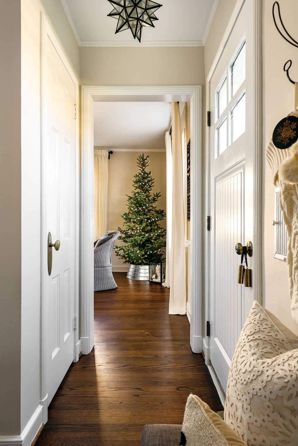Farmhouse styled hallway looking down at the Christmas tree passed the front door.