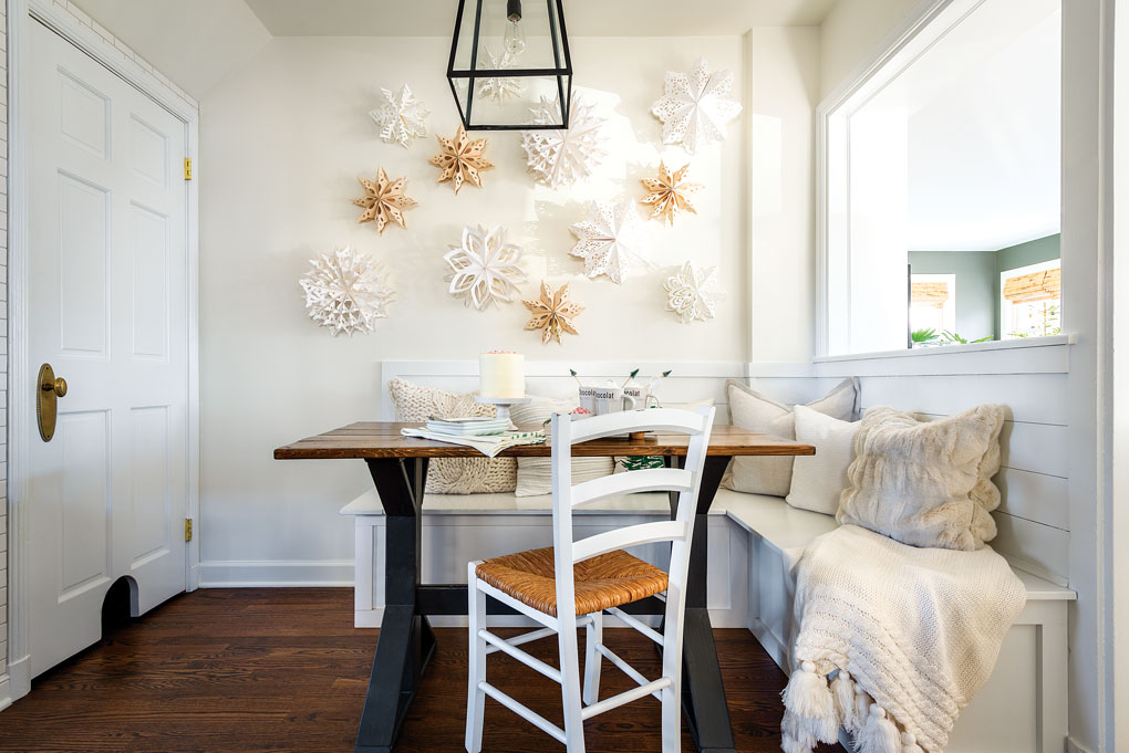 A white kitchen banquette with a wooden dining table and handmade paper snowflakes hanging on the wall.