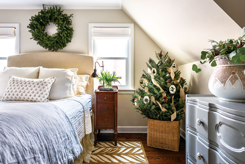 Light and bright bedroom with a mini Christmas tree in the corner and a wreath placed above the bed.