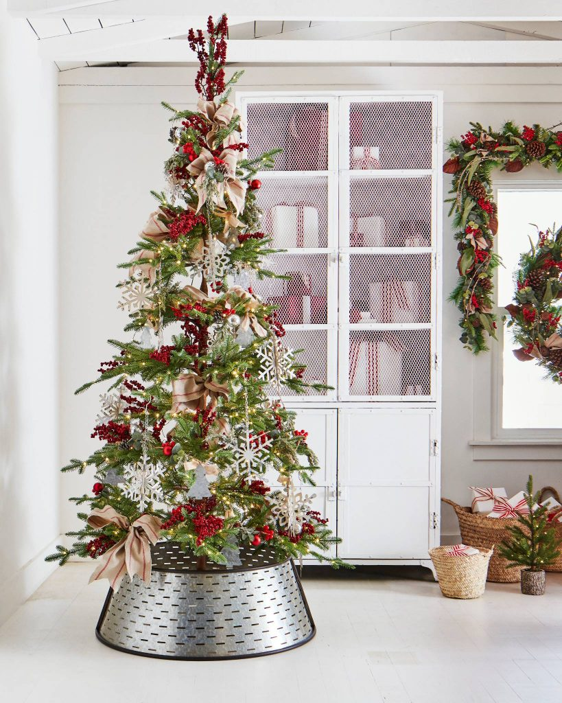 This Alpine balsam fir style tree from Balsam Hill in a white room near a white farmstyle cabinet
