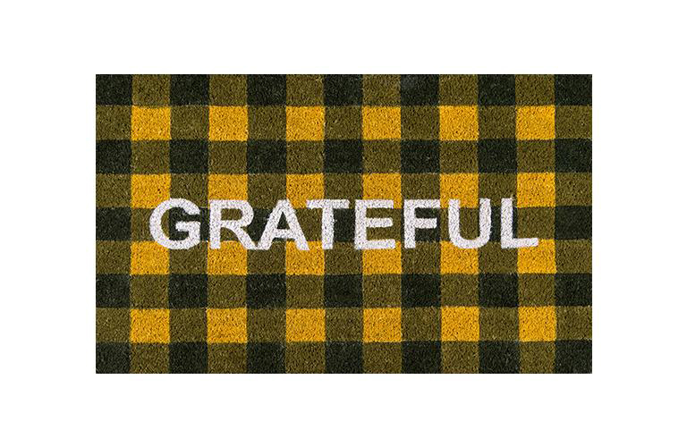 orange and black buffalo check coir mat emblazoned with the word grateful