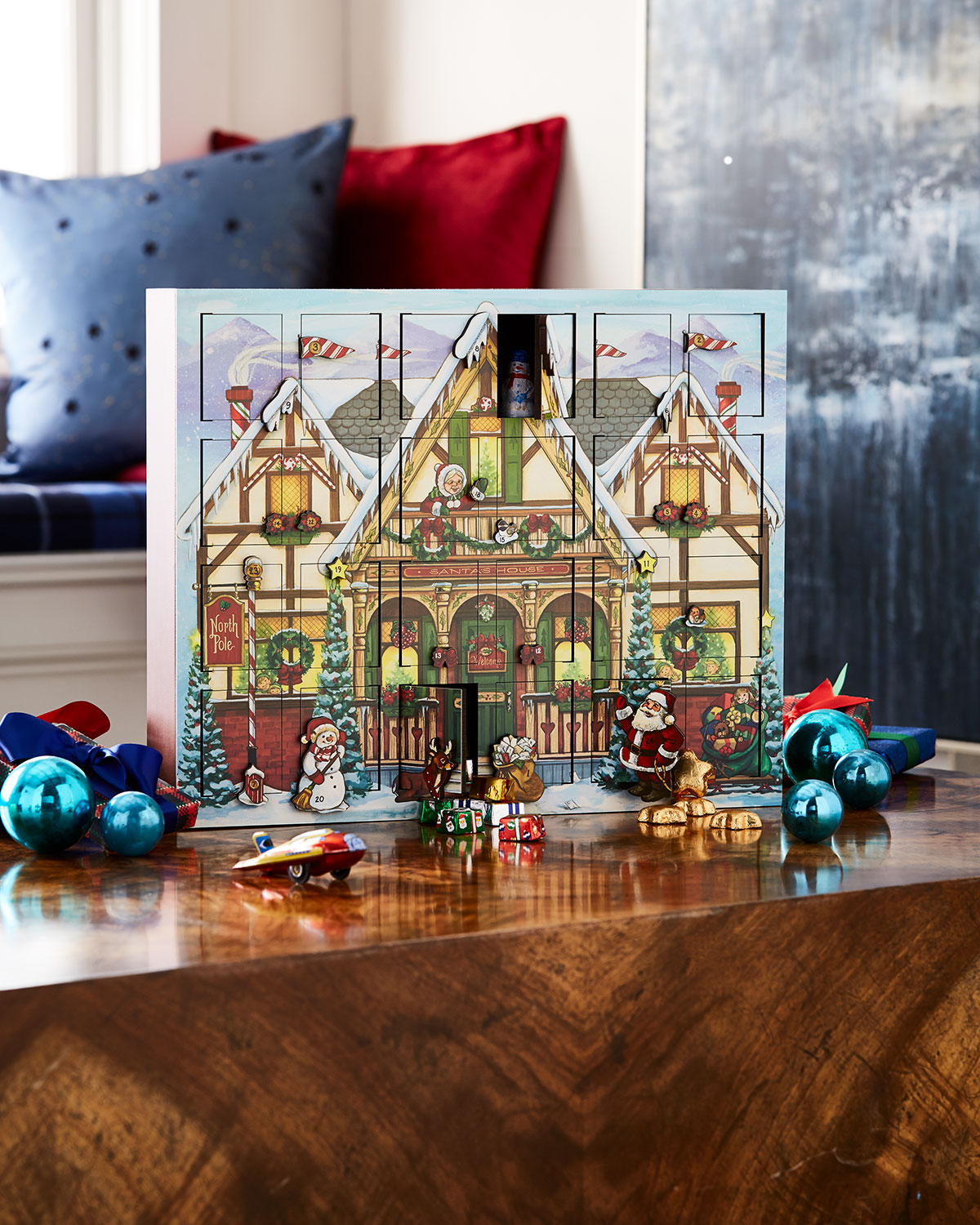 Wooden advent calendar filled with tiny ornaments, surrounded by glass ornaments and sitting on a wooden table.