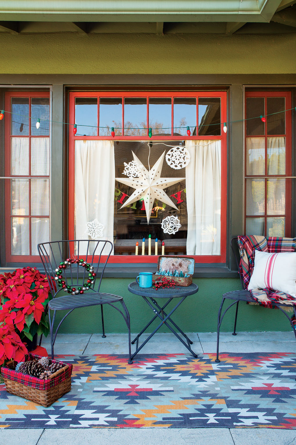 Metal black bistro set sitting on the front porch atop a Navajo inspired rug flanked by poinsettias.