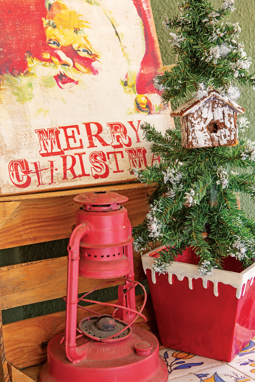 An antique piece of Santa art paired with a faux-flocked tree and a red antique lantern