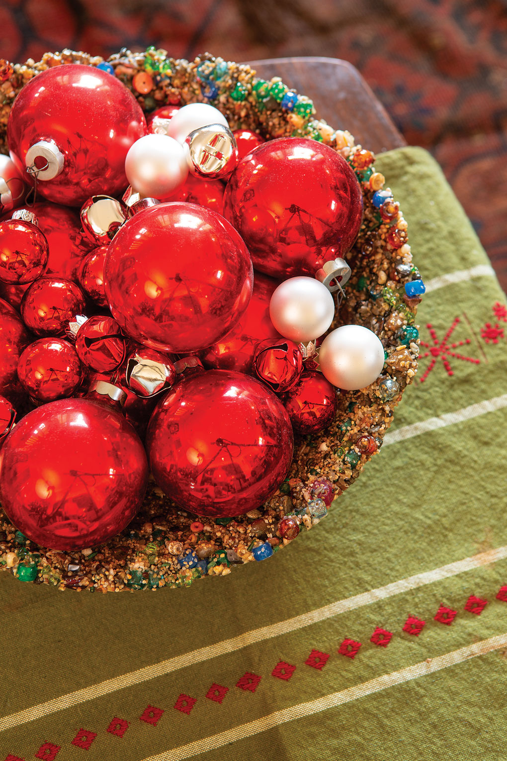 Vintage holiday table runner topped with a large centerpiece bowl filled with glass antique red ball ornaments.