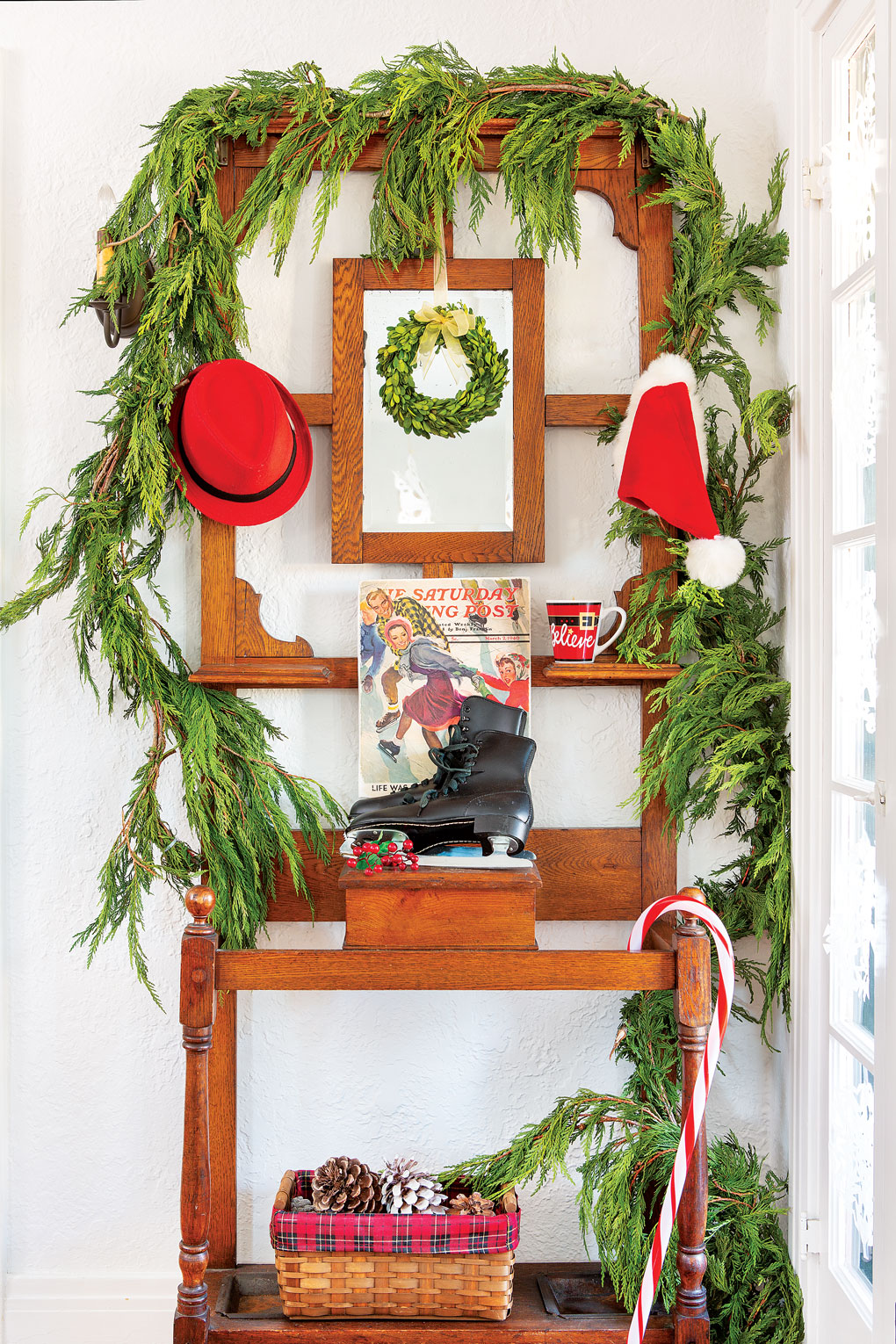 A wooden hall tree in the entryway of the home adorned with a cedar garland with pops of red and a pair of antique black ice skates.