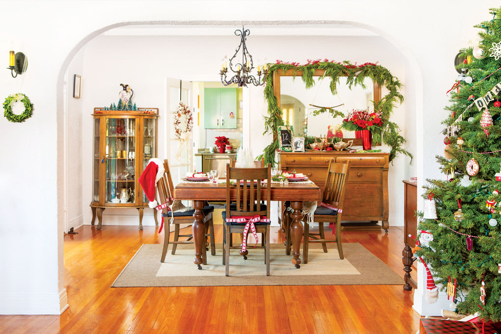 A curved arch looking through to a Christmas decorated dining room filled with antique wood furniture.