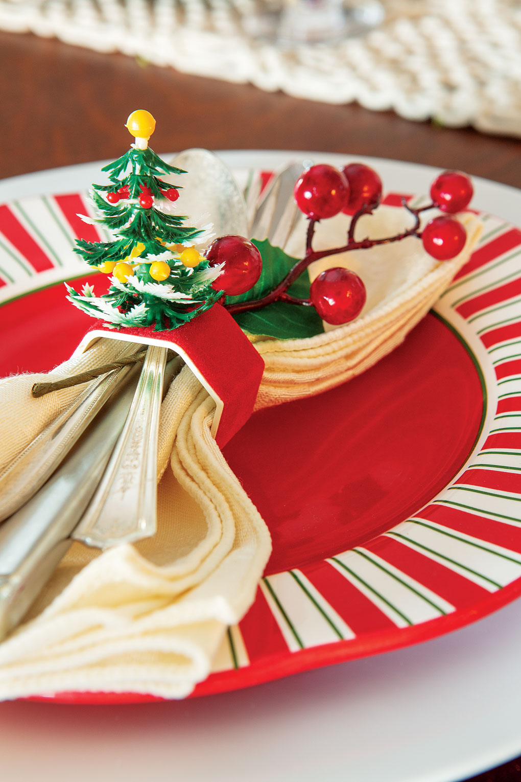 Holiday dinner place setting topped with a cream napkin and vintage napkin ring topped with a Christmas tree.
