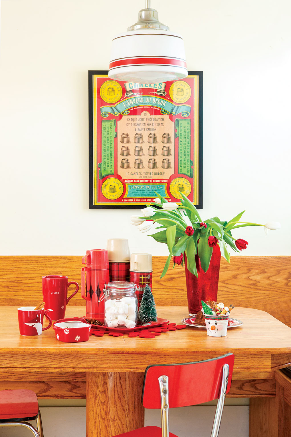 A wooden breakfast nook is adorned with red accents, a vase of red tulips and a collection of vintage thermoses.