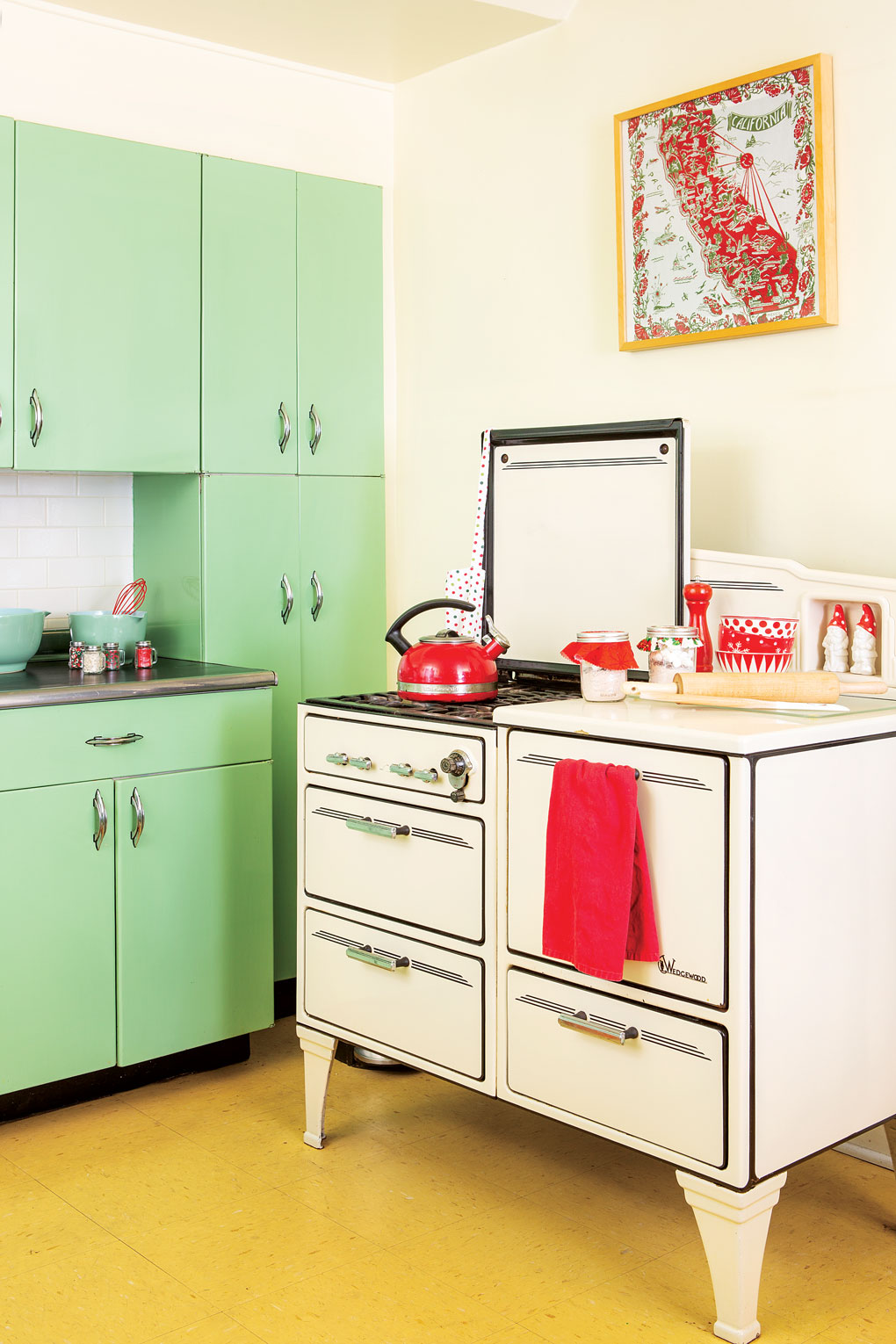 Mint green cabinetry and an antique Wedgewood gas stove in white.