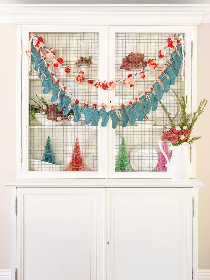 Teal and pink Christmas advent calendar made out of mini stockings, pink pom poms, and silver bells