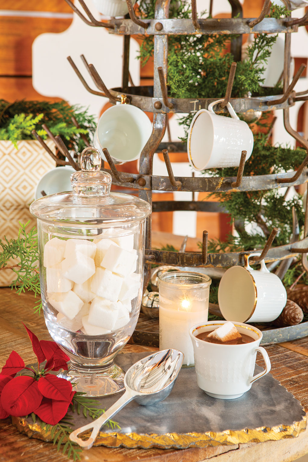 Glass apothecary jar filled with large marshmallows cubes next to a large metal mug holding tree and a cup of cocoa.