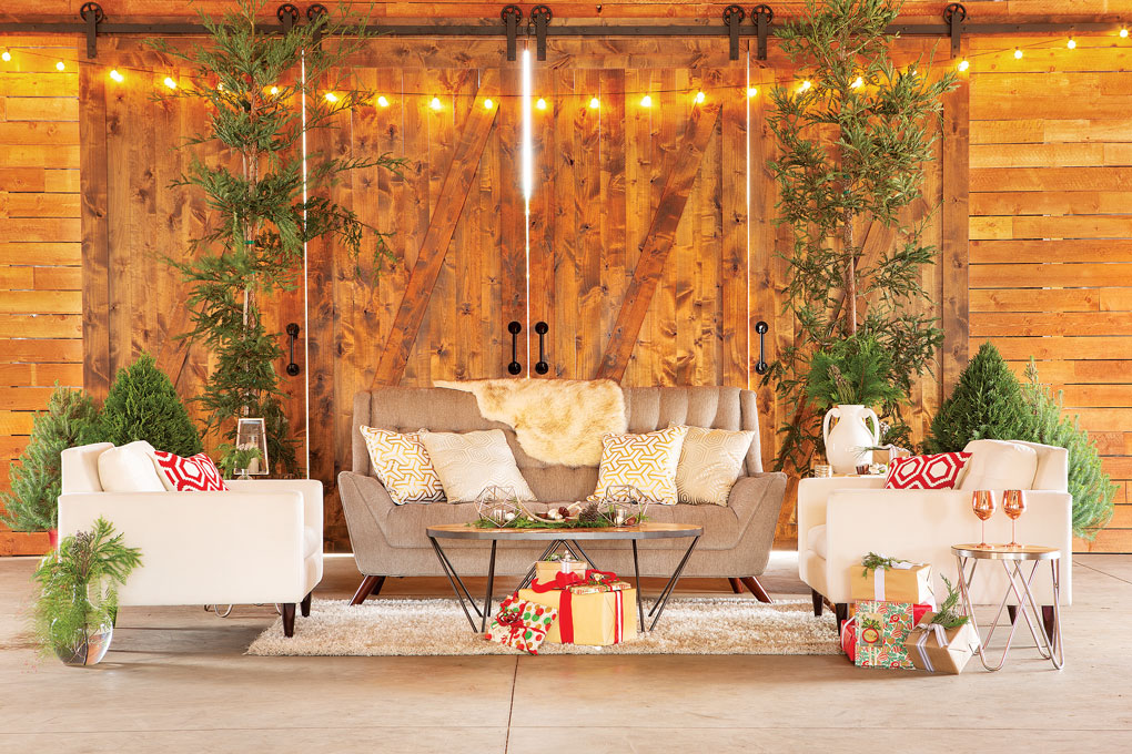 Christmas entertaining area made in a barn, flanked with miniature pines and sprinkled with gifts and pops of red.