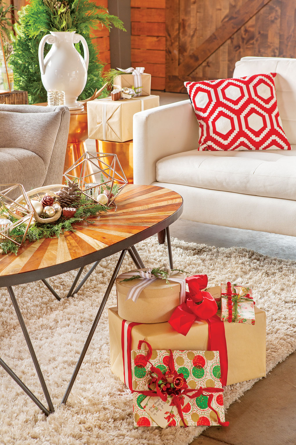 Sitting area with a light colored couch and armchair in the background and a midcentury inspired coffee table with a pile of wrapped Christmas gifts in the foreground.