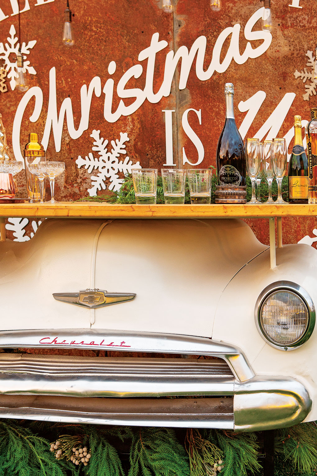 A white, genuine front end of a 1949 Chevy crafted into a barnyard bar display topped with champagne, drinks and glasses.