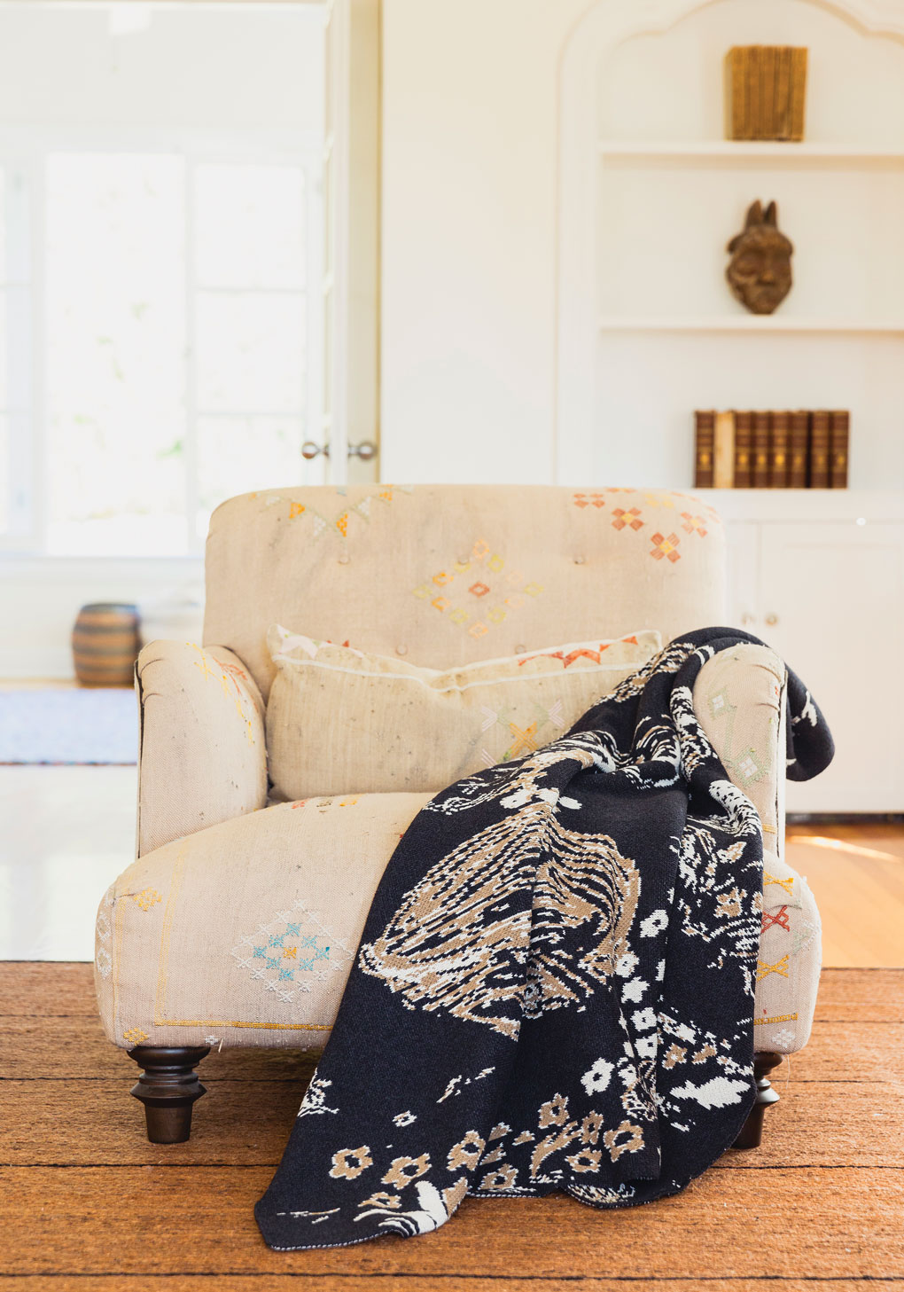 Antique looking armchair featuring a bold printed throw blanket resting over the arm.