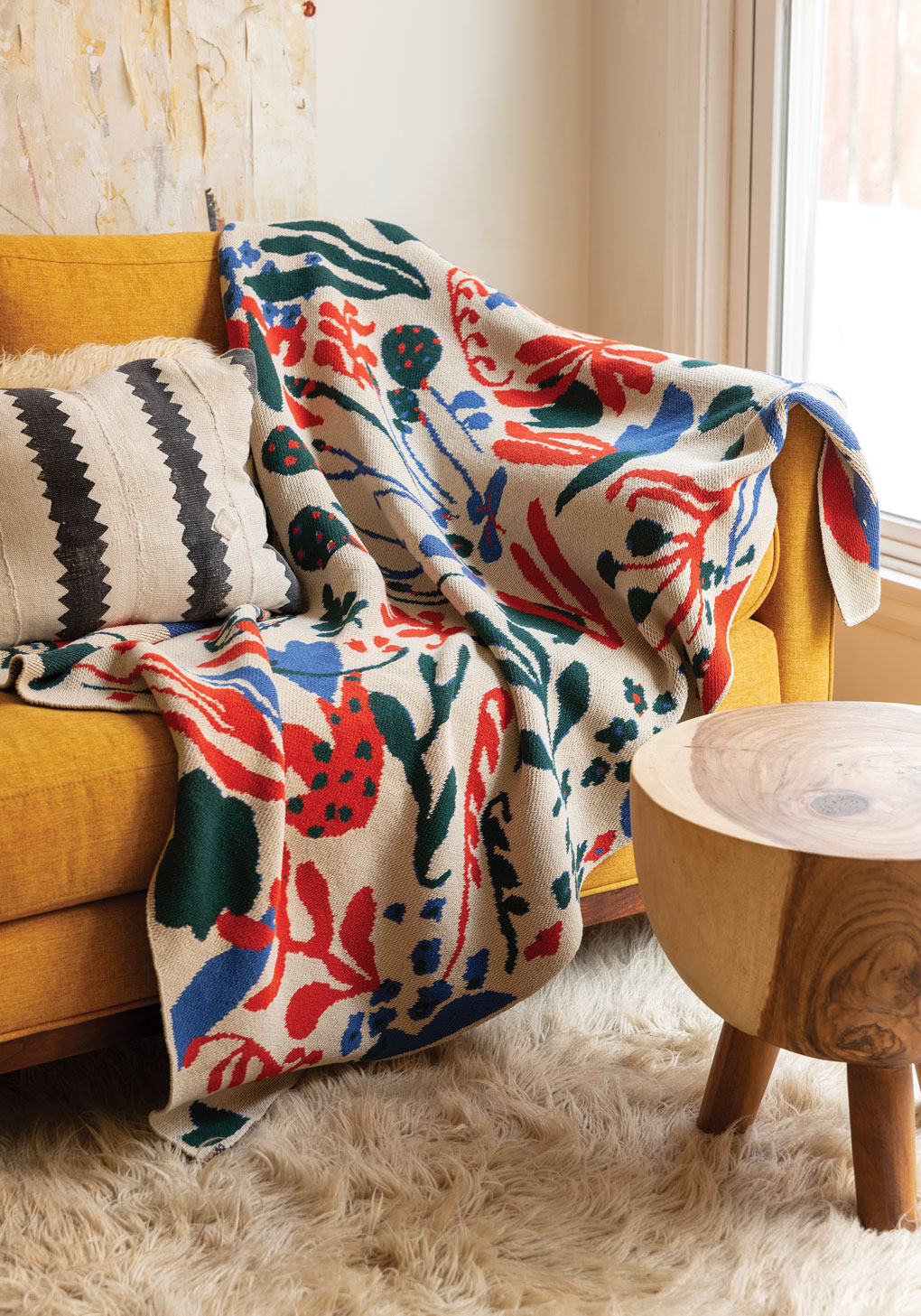Mustard colored couch with a colorful and bold throw blanket draped over the arm.
