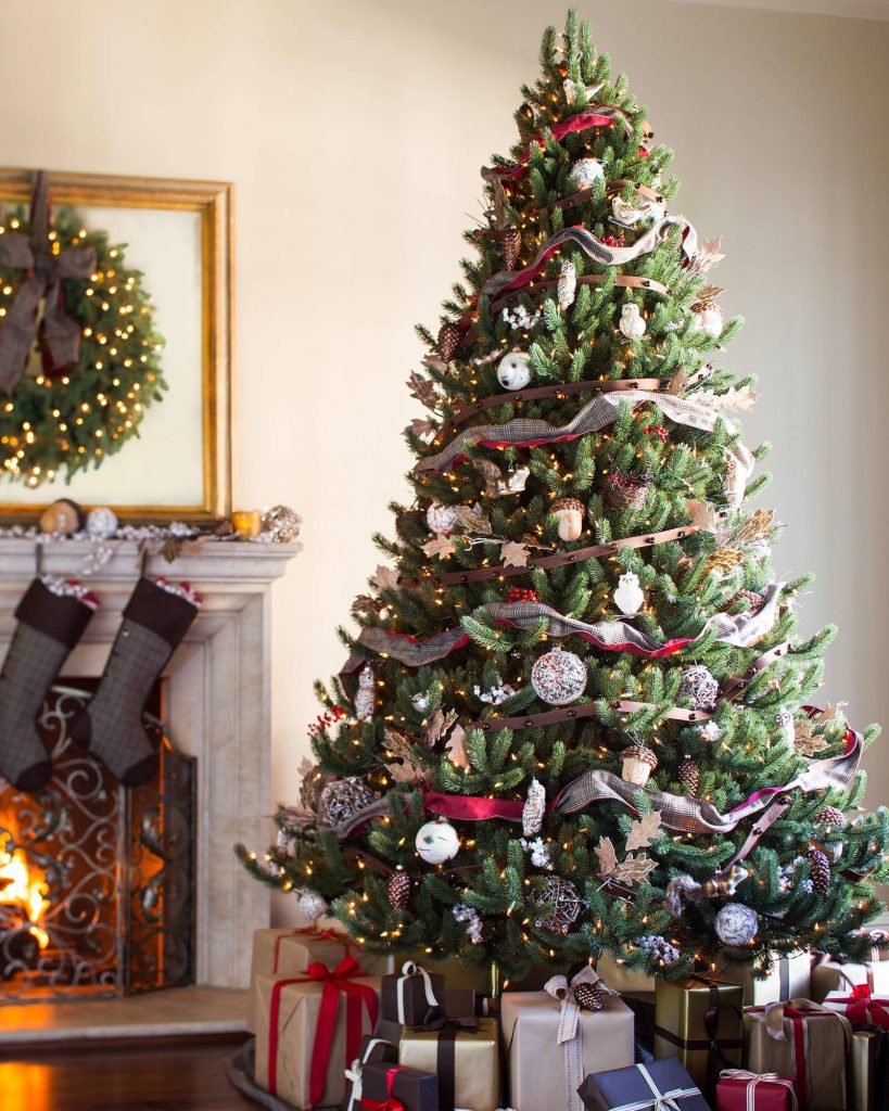 an elegnat christmas tree with ribbon garland and glass ornaments sits by a stone fireplace.