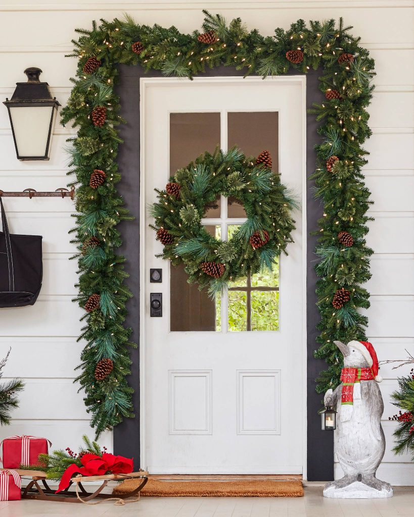 A white cottage front door with a pine garland and matching wreaths.