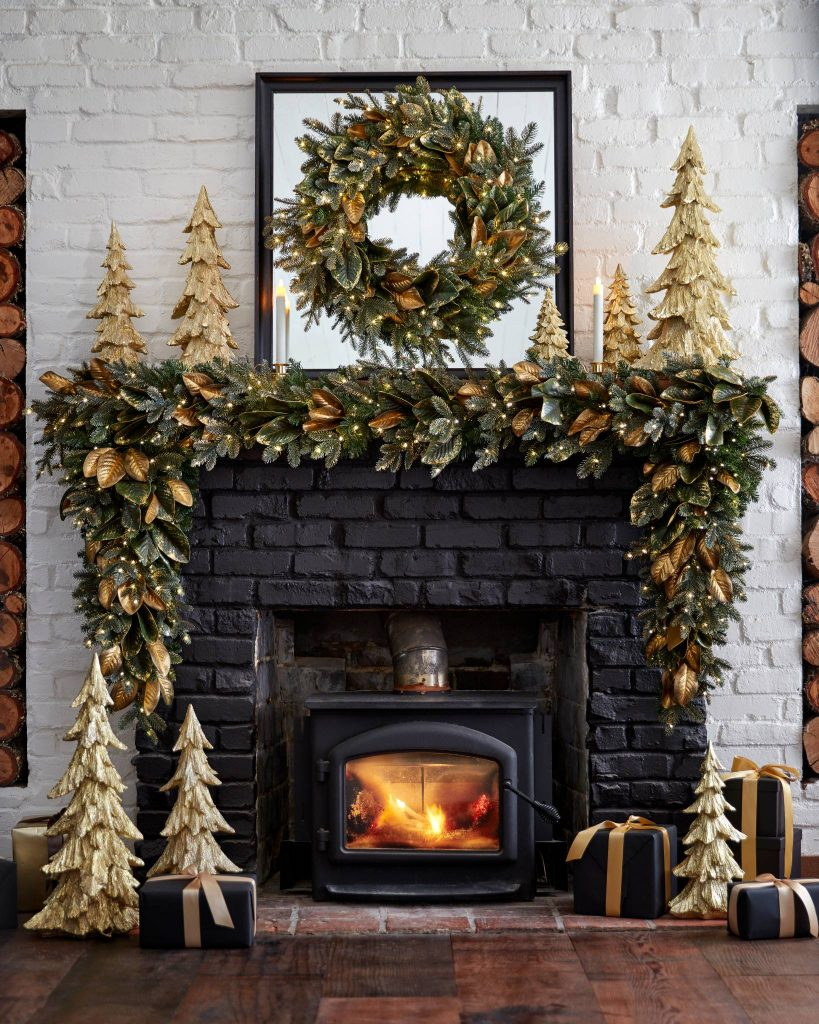 a black fireplace with gold wood trees on the mantel and hearth and a generous gilded Magnolia swag on the mantel.