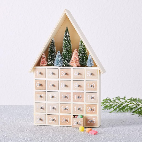 Light colored house shaped advent calendar with 25 pull out boxes and snowy, bottle brush trees at the top.
