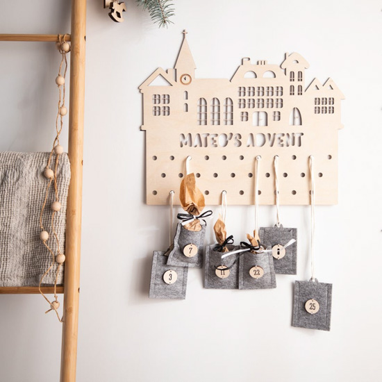 Personalized, laser cut, wooden advent calendar hanging on a white wall next to a decorative ladder.