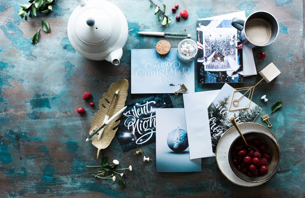 an arrangment of beautiful holiday cards on a blue painted tabletop surrounded by team, flowers and cranberries