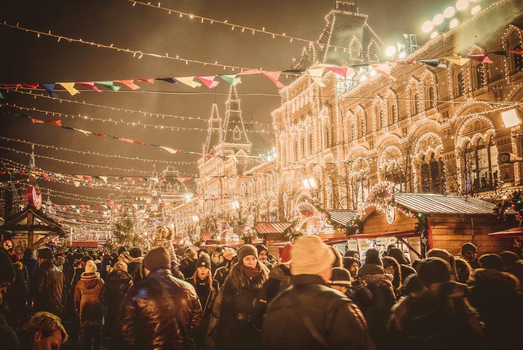 outdoor christmas market full of crowds and strings of lights hanging between small house shaped stalls.