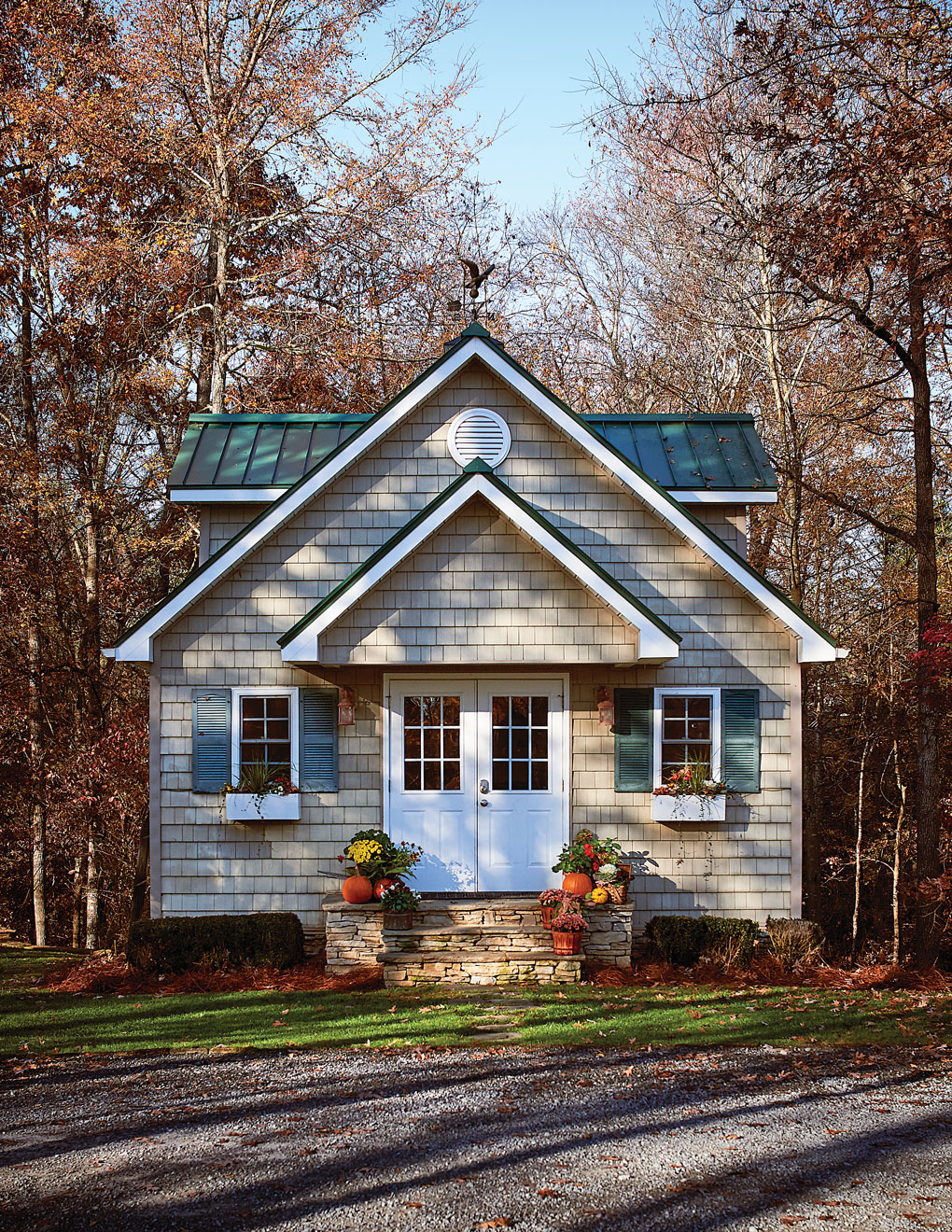 Exterior view of a cottage styled shed in the woods.