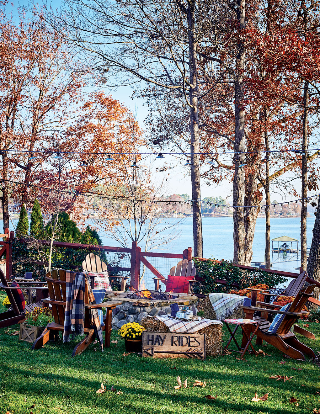 Adirondack chairs encircle a fire pit next to the lake, surrounded by trees and string lighting.