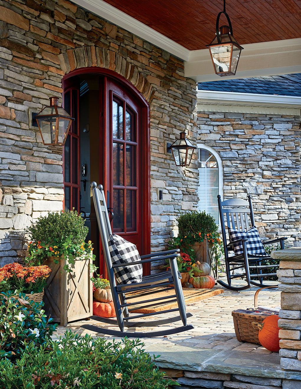 Stonework facade and deep red double front doors, flanked by black wooden rocking chairs and scattered pumpkins for a fall welcome.