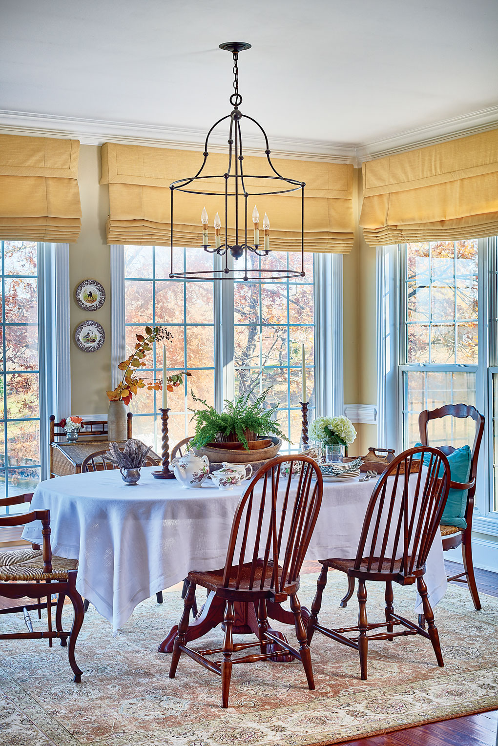 Breakfast nook surrounded by windows and a lake view with high back wooden chairs and light yellow walls and window coverings.