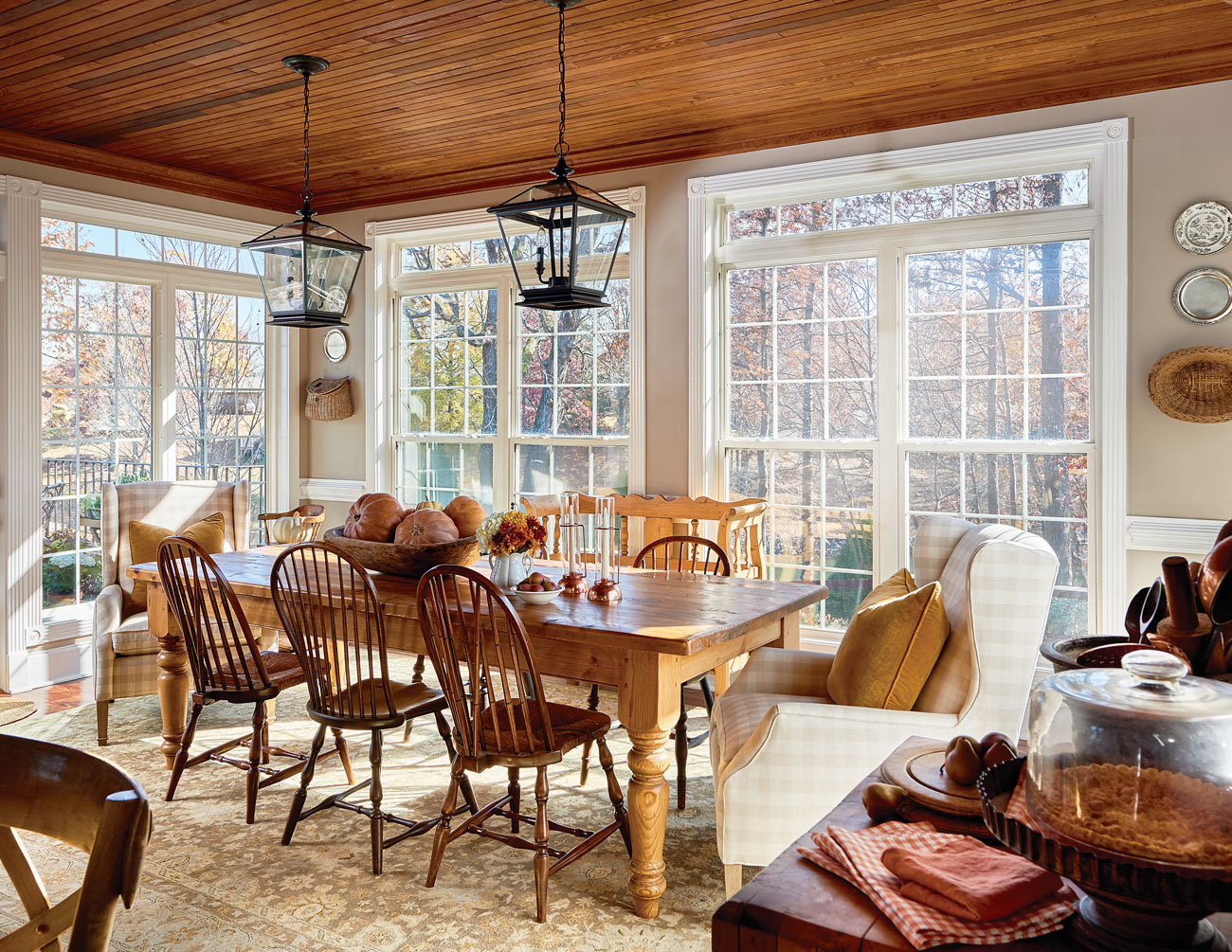 Lake house dining room with pine farm table and hanging lantern pendants overhead surrounded by a wall of windows.