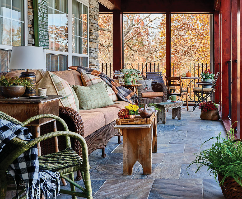 Screened in porch at a South Carolina lake house, decorated and ready for sitting and dining.