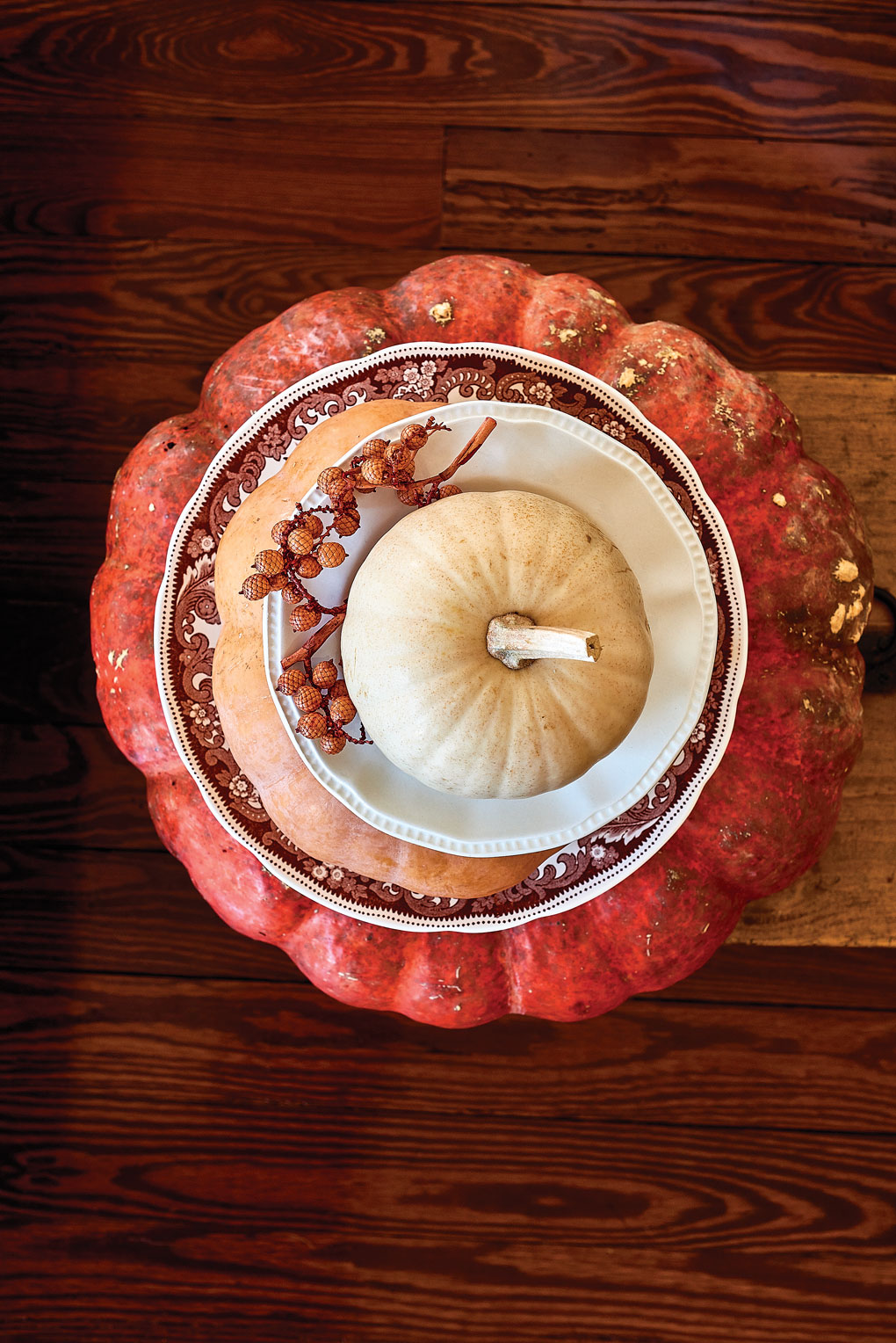 Aerial shot of a stack of layered pumpkins and fall themed china plates set on a wooden grain table.