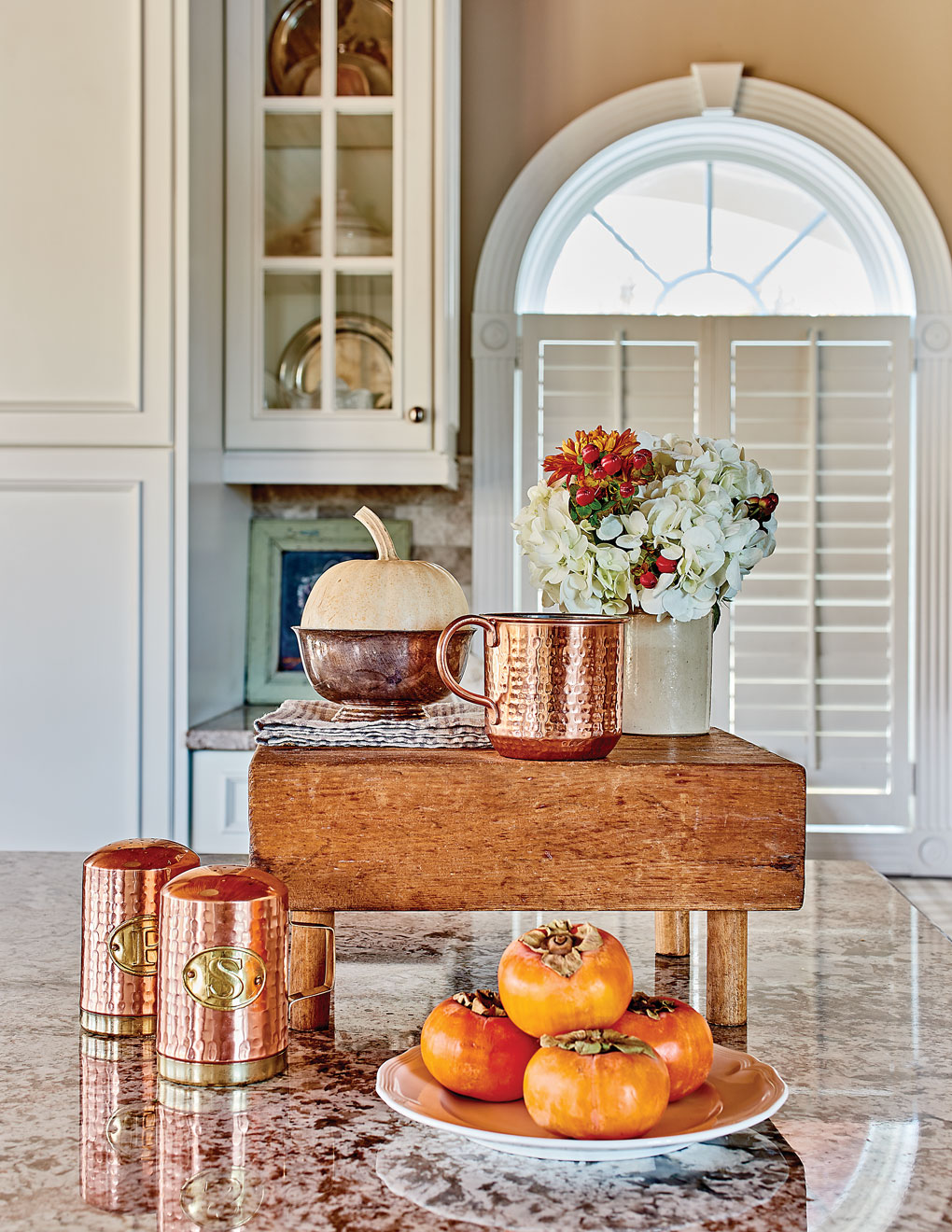 Kitchen view of a granite countertop covered with wooden butcher block display and copper accents alongside a plate of bright orange persimmons.