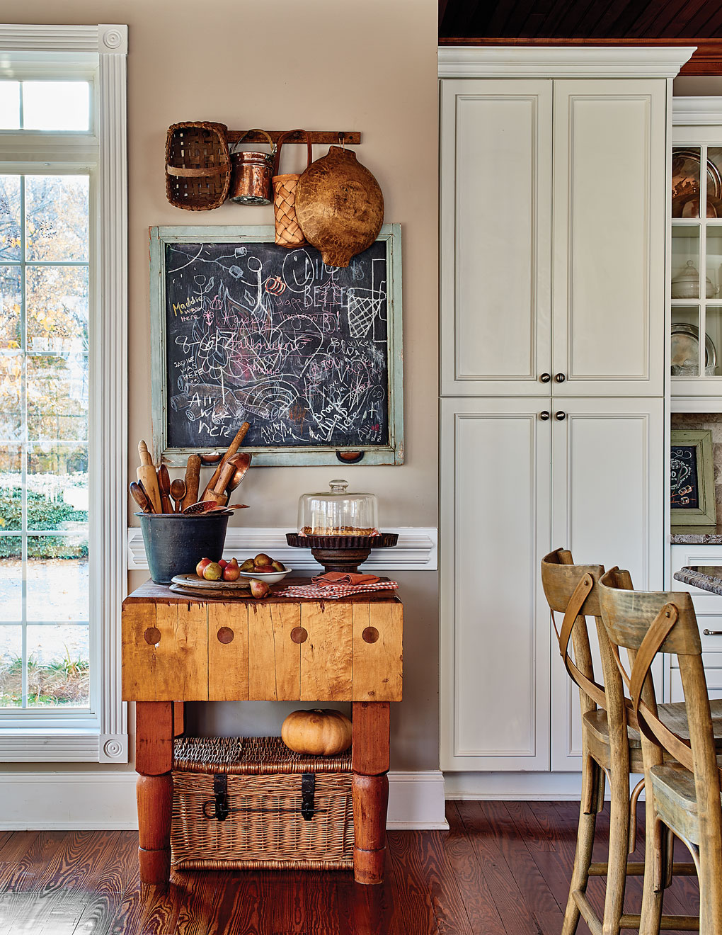 Antique butcher block in the kitchen surrounded by vintage baskets and kitchen tools and a chalkboard converted from an old window screen.