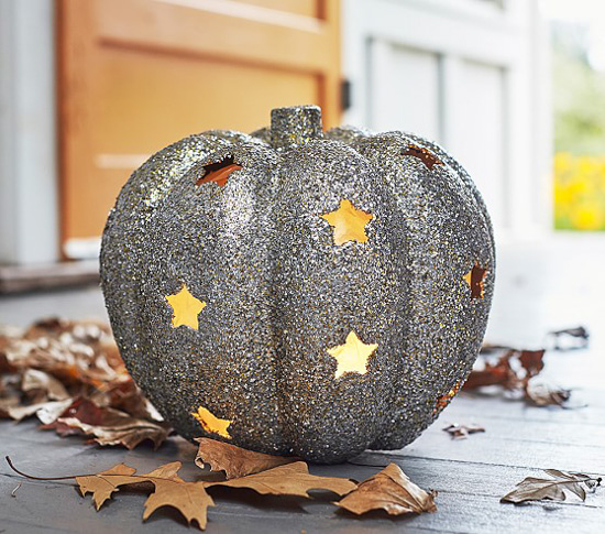 Silver glitter pumpkin with star cut-outs and light illuminating through the holes sitting on a front porch littered with fall leaves.