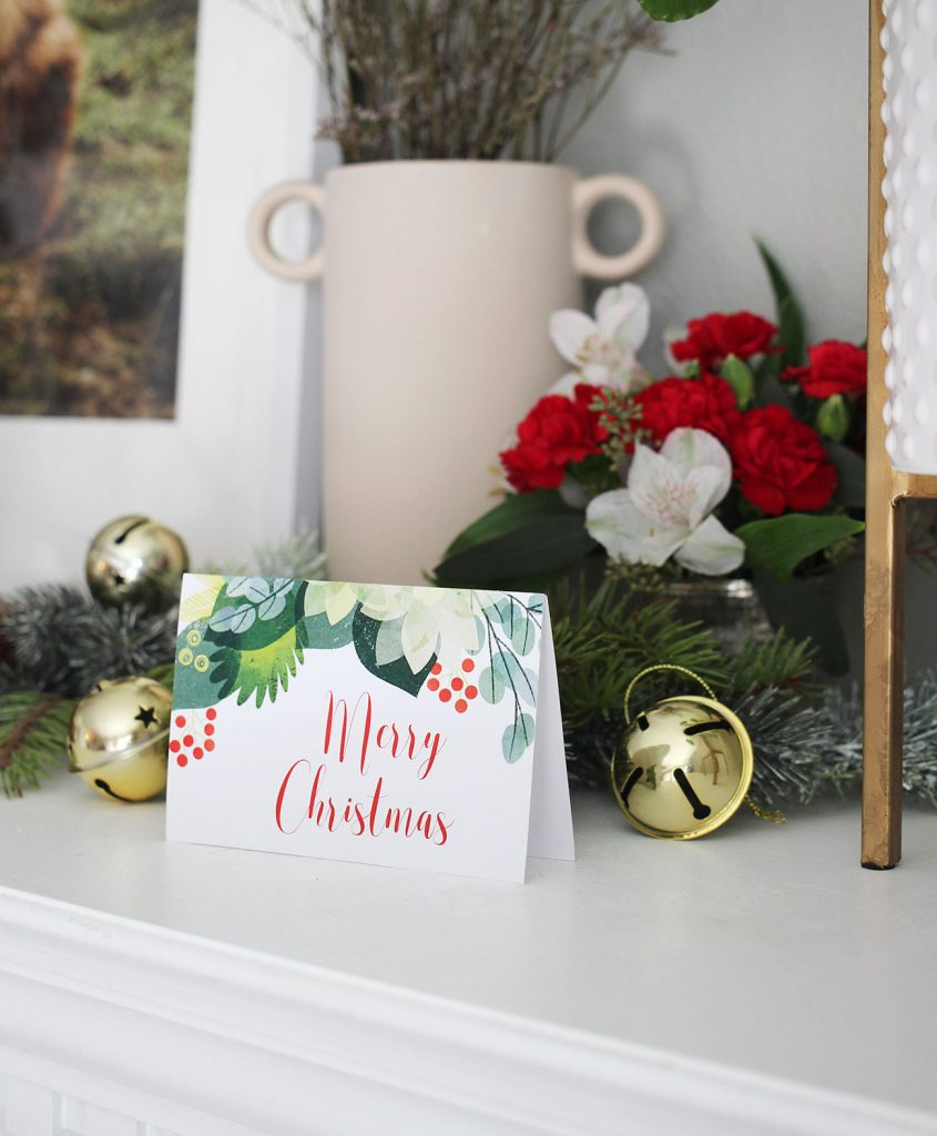 holiday card on a mantel with jingle bells