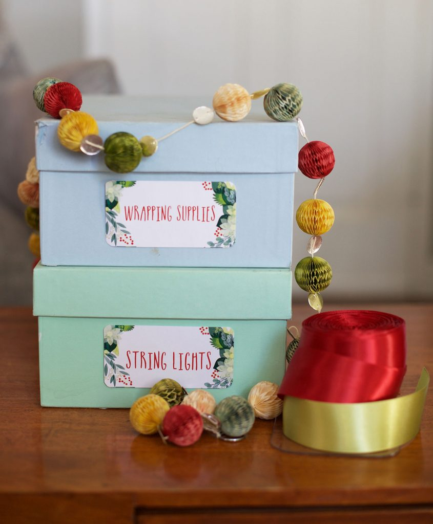 """small lidded organiing boxes are labeled with festive holiday label stickers marked """"wrapping supplies"""" and """"Sting Lights"""""""